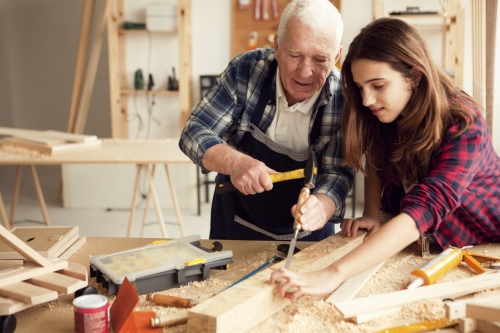 Grandpa with granddaughter enjoy  at grandpa's carpentry workshop